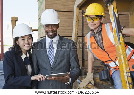 Portrait of engineers and female industrial worker smiling - stock photo