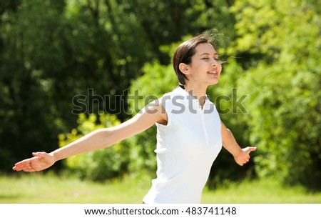 Portrait of enjoying woman raising her hands