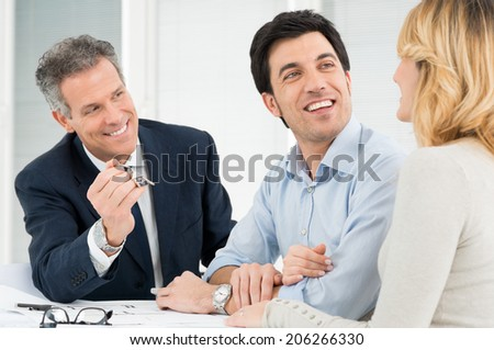 Portrait Of Estate Agent Showing New Home Keys To A Young Couple
