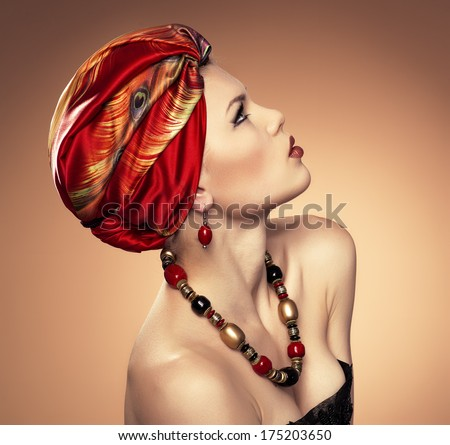 Portrait of ethnic dresses fashionable woman wearing jewelery. Young beautiful Caucasian female model with red turban looking up.  - stock photo