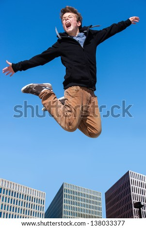 Portrait of euphoric boy jumping high in city.