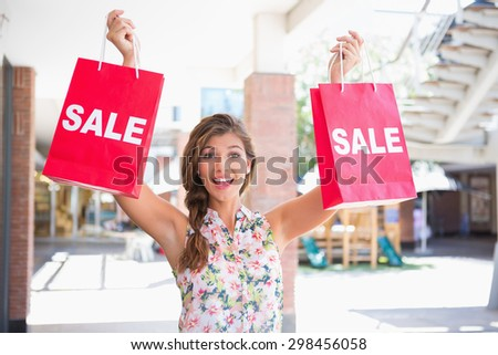 Portrait of euphoric woman holding two sale shopping bags at the shopping mall - stock photo