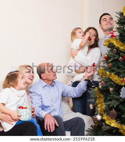 Portrait of european family decorate the Xmas tree in appartment - stock photo