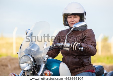 Portrait of European woman motorcyclist sitting on chopper in leather jacket and white safety helmet, outdoor