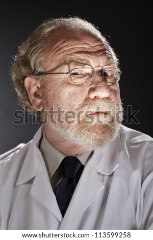 Portrait of evil doctor in lab coat and necktie with sinister expression. Dark background and dramatic low angle spot lighting create spooky shadows on face. - stock photo
