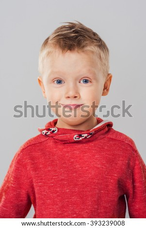 Portrait of excited and surprised child boy. Child expressing surprise and happiness over gray background - stock photo