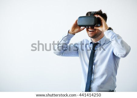 Portrait of excited businessman in vr goggles - stock photo