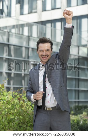 Portrait of excited businessman with arm raised celebrating success outside office building - stock photo