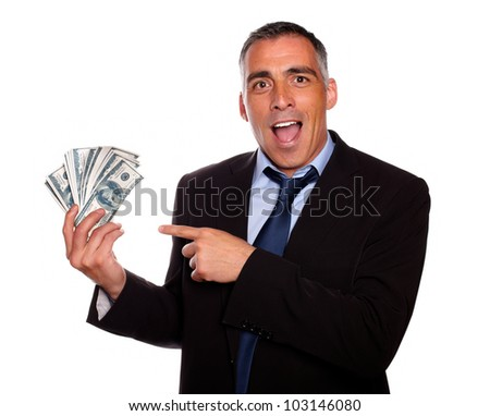 Portrait of excited executive holding and pointing cash money on isolated background - stock photo