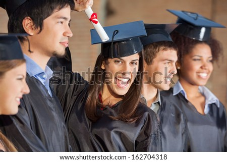 Portrait of excited female student holding certificate while standing with friends at college