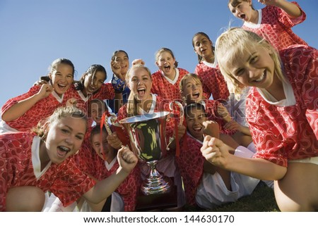 Portrait of excited girls' soccer team holding trophy against clear sky - stock photo