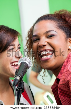 Portrait of excited singer with colleague performing in recording studio