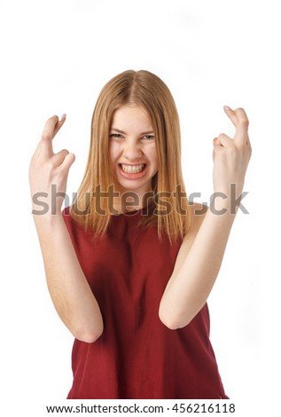 Portrait of excited woman crossing fingers against white background.