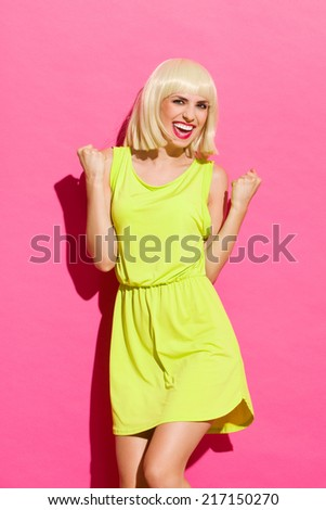 Portrait of excited woman. Smiling blond girl in lime dress gesturing success with fists raised in the air. Three quarter length studio shot on pink background. - stock photo