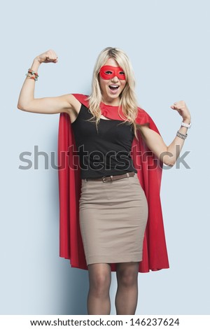 Portrait of excited young blond woman in superhero costume flexing arms over light blue background - stock photo