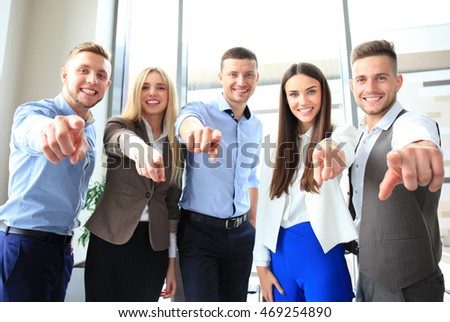 Portrait of excited young business people pointing at you