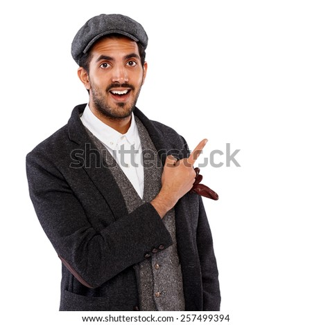 Portrait of excited young indian man pointing at copyspace on white background - stock photo