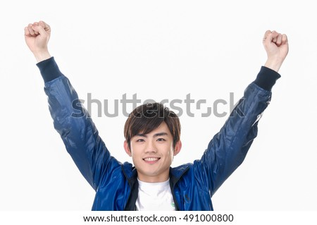 Portrait of excited young man clenching fists isolated