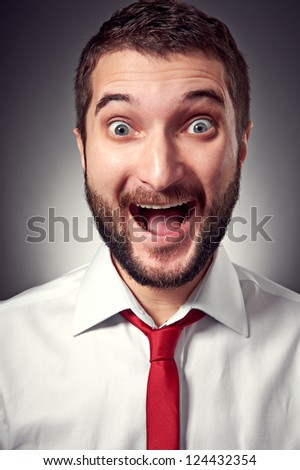 portrait of excited young man with beard over grey background