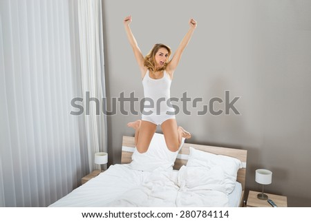 Portrait Of Excited Young Woman Jumping On Bed - stock photo