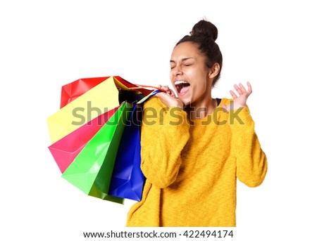 Portrait of excited young woman with shopping bags standing on white background