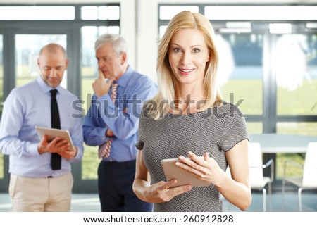 Portrait of executive business woman with digital tablet standing at office while business people discussing at background. - stock photo