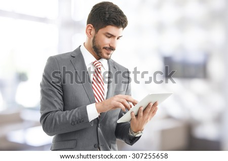 Portrait of executive businessman standing at office and holding hand digital tablet. Young professional touching the screen and checking e-mails on tablet.