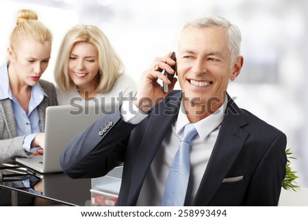 Portrait of executive businessman using his phone while business team working at background.  - stock photo