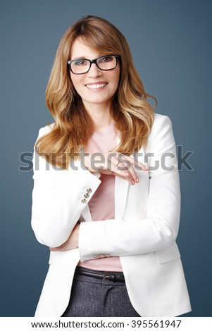 Portrait of executive businesswoman looking at camera and smiling while standing at isolated background.