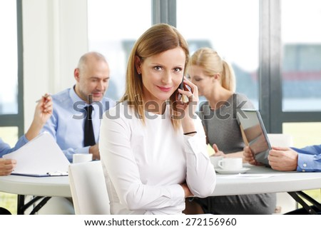 Portrait of executive businesswoman making call while sitting at meeting. Sales team sitting at background and working on presentation. Teamwork at office. - stock photo