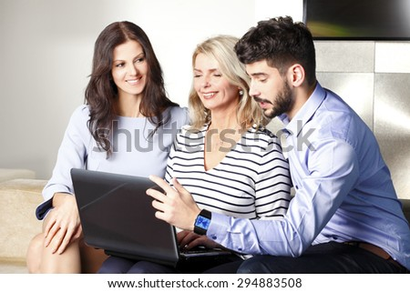 Portrait of executive businesswoman sitting at office with laptop while business people sitting next to her. Business team working together on presentation.