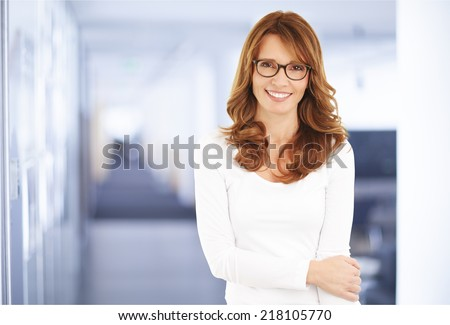 Portrait of executive businesswoman standing at office. - stock photo