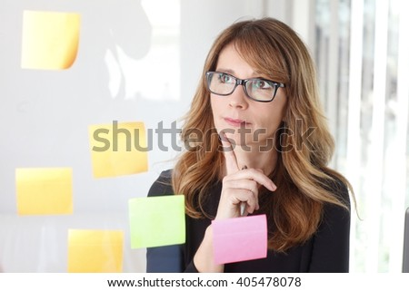 Portrait of executive businesswoman thinking a new idea while standing in front of transparent idea board at office.