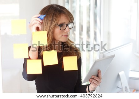 Portrait of executive businesswoman using digital tablet and writing on a post-it stuck to a glass wall.