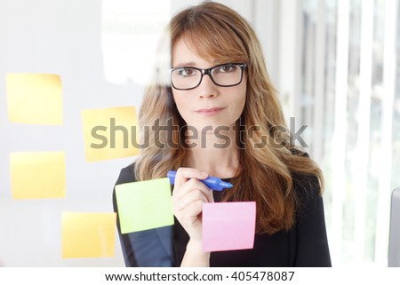 Portrait of executive businesswoman writing on a post-it stuck to a glass wall.