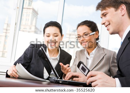 Portrait of executive employees looking at laptop monitor and discussing new project during meeting