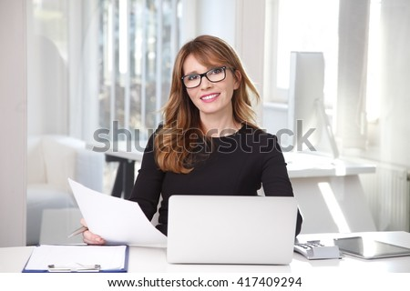 Portrait of executive financial manager holding document in her hand while working on laptop at office.