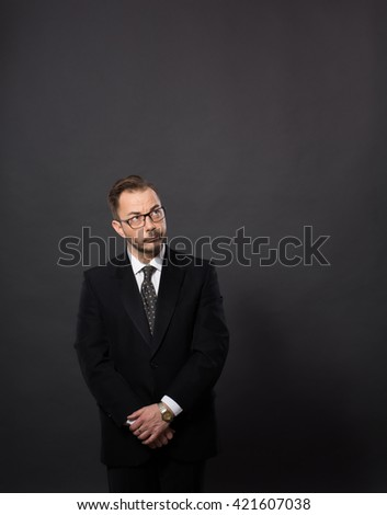 Portrait of executive officer in glasses posing for photographer. Businessman in black suit looking away in studio.