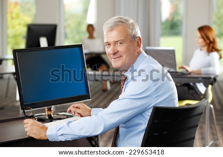 Portrait of executive old sales man sitting at office while using computer. Business people. - stock photo