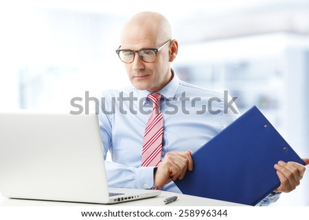 Portrait of executive sales man sitting in front of computer while holding file in his hand. Businessman working at office. - stock photo