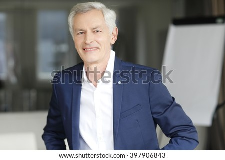 Portrait of executive senior businessman sitting at office and working.
