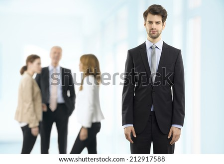Portrait of executive young businessman standing at office background with colleagues. Business people. - stock photo