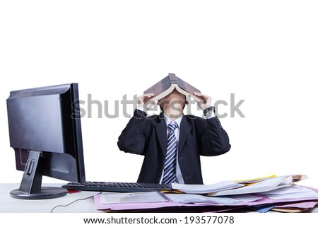 Portrait of exhausted businessman because overworked covering his face by a book - stock photo