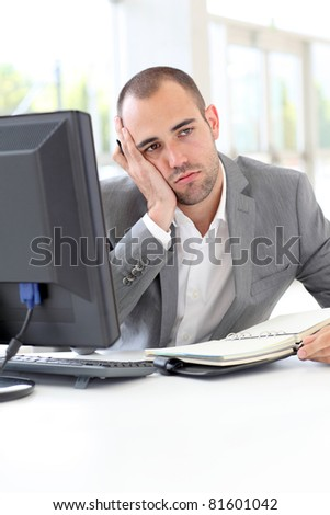 Portrait of exhausted businessman in office
