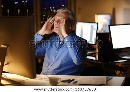 Portrait of exhausted businessman sitting at office in front of computer and holding his head with two hands while working late night.  - stock photo