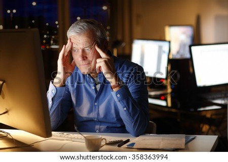 Portrait of exhausted senior professional man thinking about how to solve the problem while sitting at office in front of computer and working late.  - stock photo