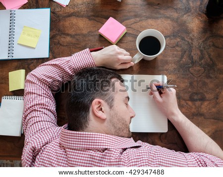 portrait of exhausted worker sleeping on his desktop - stock photo