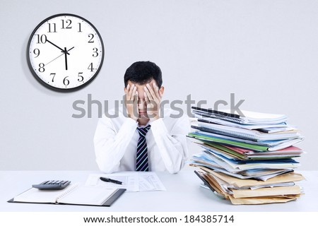 Portrait of exhausted young businessman sitting at office desk - stock photo