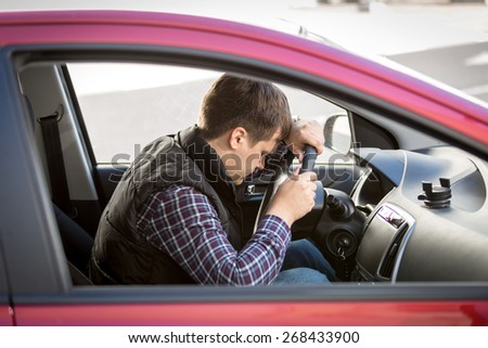 Portrait of exhausted young man sleeping on drivers seat while driving a car - stock photo