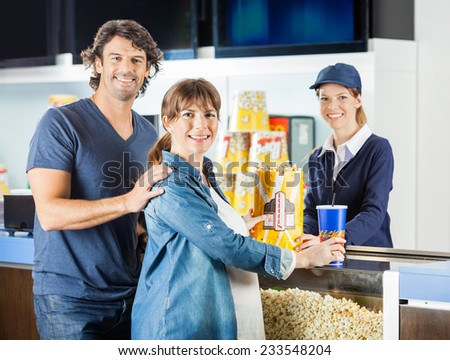 Portrait of expectant couple buying popcorn and drink from female seller at cinema concession stand - stock photo